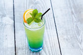 Blue green cocktail with orange and mint — Stock Photo