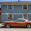 Постер, плакат: Old fashioned red car on the background of the blue wooden house