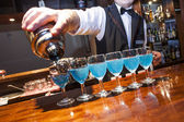 Barman pouring blue coloured drinks to the glasses on the bar co — Stock Photo