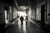 A girl and a boy walking in the old town street at night, haldin — Stock Photo