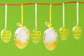 复活节装饰蛋挂在绿色背景上的红色字符串. — 图库照片