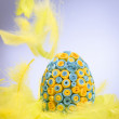 Yellow and blue Easter egg lying in yellow feathers, feathers fa — Stock Photo #41743659