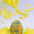 Yellow and blue Easter egg lying in yellow feathers, feathers fa — Stock Photo #41743707