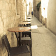 Stock Photo: Empty narrow street of old town with caffee tables outdoors.