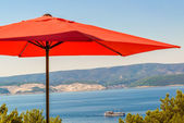 Summer terace with red umbrella. — Stock Photo