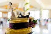 Funny wedding cake docoration, tied groom on bride's leash. — Stock Photo