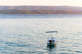 Single boat in sea, visible mountains and island coast. — Stock Photo