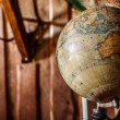 Old damaged globe against wooden wall. — Stock Photo #43089561