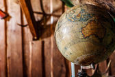 Old damaged globe against wooden wall. — Stok fotoğraf