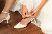 Fragment of woman's arm and hands fastening white wedding shoes. — Stock Photo