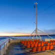 Orange outdoor deck chairs on ferry sailing in frozen sea. — Zdjęcie stockowe #44283831