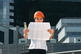 Woman architect inspecting the blueprints — Stock Photo