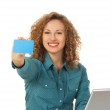 Woman holding card with a laptop in front — Stock Photo