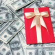Stock Photo: Gift on dollars background
