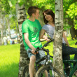 Couple riding bikes in the wood — Stok fotoğraf