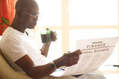 African American with newspaper — Stock Photo
