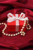Gift on red silk satin — Foto de Stock