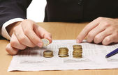 Businessman putting the coins in columns — Stock Photo