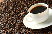 A cup of coffee and coffee beans — Stock Photo