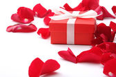 A gift and red rose petals — Stock Photo