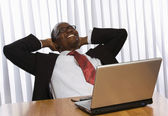 African American sitting on the desk with laptop — Stock Photo