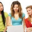 Three girls sitting on the floor with a laptop — Stock Photo #41151479