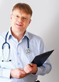 Male doctor standing with folder — Stock Photo
