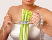 Woman with vegetables and measuring tape — Stock Photo