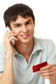 Man with a mobile phone and a card — Stock Photo