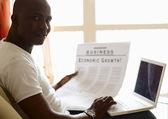 Afryki amerykański z gazety i laptopa — Zdjęcie stockowe