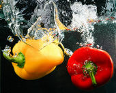 Red and yellow peppers in water — Stock Photo