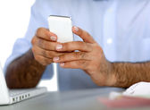 Man at the desk using mobile phone — Stock Photo
