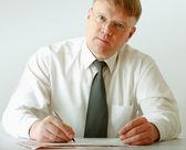 Biznesmen siedzi na biurku i pisania — Zdjęcie stockowe