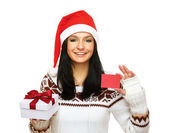 Woman in santa hat holding gift box and credit card — Stock Photo
