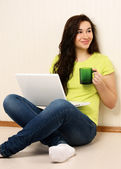 Girl with laptop and holding cup — Stock Photo