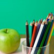 Glass with pencils and green apple, — Stock Photo #41182679