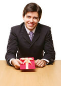 Businessman offering a gift to you — Stock Photo