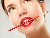 Woman's lips holding make up brush — Stock Photo