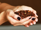 Hands cupped holding coffee beans — Stock Photo