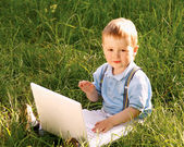 Child with laptop in nature — Stock Photo