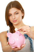 Woman standing with piggy bank — ストック写真
