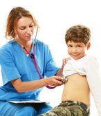 Female doctor is examining boy with a stethoscope — Stock Photo