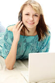 Woman  with a laptop  and talking on the phone — Stock Photo