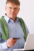 Man with a laptop and credit card — Photo
