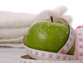 Green apple and a measuring tape — Stock Photo