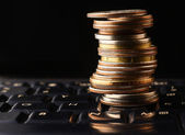 Pile coins on keyboard — Stock Photo