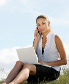 Woman with a laptop and phone — Stock Photo