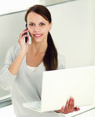 Woman with laptop and talking on the phone — Stock Photo