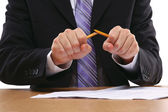 An angry businessman breaking a pencil — Stock Photo