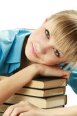 Young female student lying on books — Stock Photo